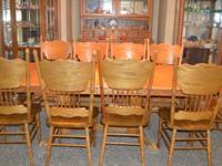 Solid oak dining room table with 10 chairs. 4 of the