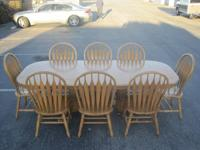 This is an Oak table with 8 chairs and 2 leaves.