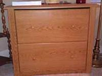 "Two drawer file cabinet. Oak finish. 22' X 34"" Holds"