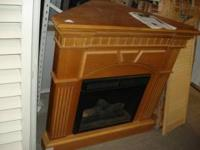 Oak corner fireplace with mantel and electric