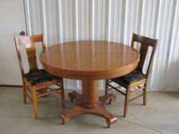 Oak pedestal table with two leaves and four chairs.