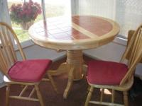 This pedestal table is round with a terra cotta inlaid