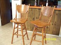WE HAVE TWO OF THESE OAK BAR STOOLS THAT SWIVLE BOTH