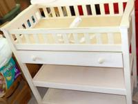 Changing table is made out of wood and is off-white. It