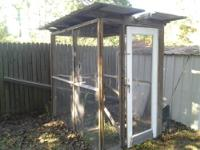 Large wood frame with wire mesh and tin roof. Walk in