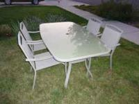 Outdoor dining set includes glass table and 4 chairs.