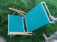 Have a green cloth folding chair with wooden armrests.