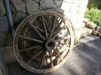 Two antique wagon wheels, wooden spokes with metal