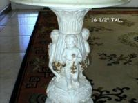 This vintage pedestal table has 3 cherubs around the