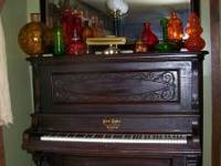 This is a beautiful Antique upright grand piano. Played