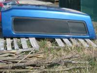 Blue ARE long-bed pickup truck topper/canopy. Two