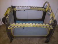 This gray and yellow play yard provides a secure and