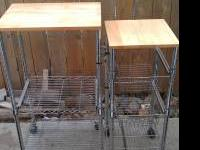 Two metal carts with wood cutting board on top very