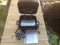 A unused portable tabletop gas grill. Grill is