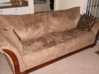 This sofa has a beige microfiber with cherry wood