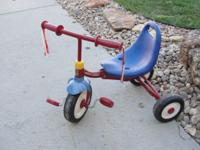 A classic! A red and blue Radio Flyer Tricycle !