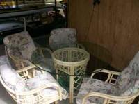 selling my rattan glass top table and 4 chairs . in