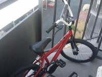 Red kids bike, not used much but is sitting outside