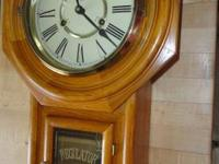 This oak wall clock states REGULATOR in gold reverse