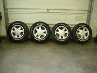 4 aluminum Ford mustang rims with tires. Tires are a