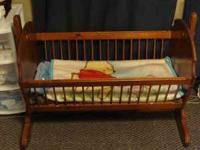 For sale is a Baby cradle. It rocks and has a pin on