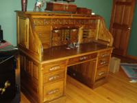 This is a modern, full size, oak, roll-top desk. The