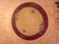 "Round area rug that measures between 70""-72"" and"