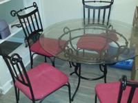 A like-new dining set with a round glass-top and metal