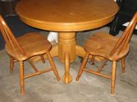 Round pedestal light oak table with one leaf and 4