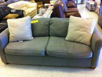 Comfy sage green couch with two cream colored pillows.