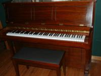A Samick studio upright piano in walnut satin. This