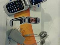 Small, older flip phone by Samsung with charger cord.
