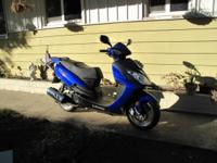 This scooter/motorcycle is blue, has 104 miles on it.