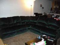 Dark green sectional couch, one side reclines and the