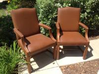 This is a set of 2 brown vinyl arm chairs with wooden