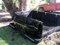 This is a black short bed step side GMC truck bed. It
