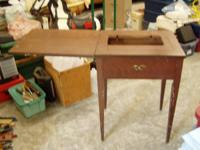This is an older small brown wooden sewing table. It