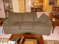 Dark green sofa with decorative pillows--seats 3