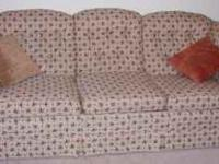 Beige sofa with blue/mauve flower pattern. Although