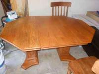 Solid oak dinning table with a leaf and six chairs, (2