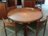 This is a solid teak pedestal dining-room table with 4