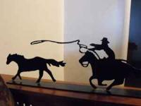 western metal decorative piece of a cowboy roping a
