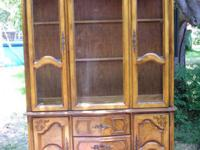 Golden Oak china cabinet that is lighted. It has 2