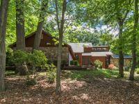 Privately situated on a 5+ acre hillside, this 3