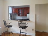 Unit features include open kitchen, full bath, hardwood