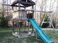 Swing set with playhouse. Includes slide, three swings,