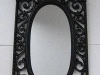 Vintage 1969 Syroco oval wall mirror in an ornate black