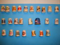 25 porcelain thimbles displayed on a wooden hanging