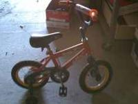 "Toddler ""Rockit"" Huffy bicycle with training wheels."