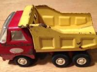 A vintage red and yellow Tonka dump truck. It has